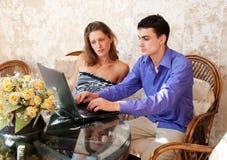 Pares jovenes que miran la computadora portátil Imagen de archivo