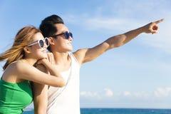 pares jovenes que miran la opinión sobre la playa Imágenes de archivo libres de regalías