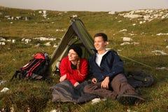 Pares jovenes que miran la puesta del sol mientras que acampa en las montañas Imagen de archivo