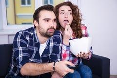 Pares jovenes que miran la TV o la película en casa Imágenes de archivo libres de regalías