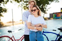 Pares jovenes que miran soñador a un lado con por otra parte rojas y azules las bicicletas Muchacho pensativo que se coloca con l Fotos de archivo