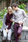 Pares jovenes que miran su Smartphone foto de archivo libre de regalías