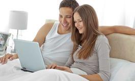 Pares jovenes que miran un vídeo en la computadora portátil Fotos de archivo libres de regalías