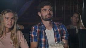 Pares jovenes que miran una película en el cine Fotos de archivo libres de regalías
