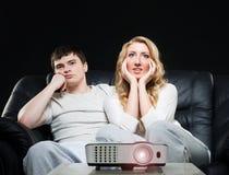Pares jovenes que miran una película mientras que se sienta en un sofá Foto de archivo libre de regalías
