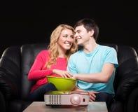 Pares jovenes que miran una película mientras que se sienta en un sofá Imágenes de archivo libres de regalías