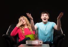 Pares jovenes que miran una película mientras que se sienta en un sofá Imagen de archivo