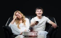Pares jovenes que miran una película mientras que se sienta en un sofá Imagen de archivo libre de regalías