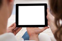 Pares jovenes que miran una tableta junto Imagen de archivo