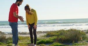 Pares jovenes que obran recíprocamente con uno a cerca de la playa en un día soleado 4k almacen de metraje de vídeo
