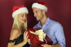 Pares jovenes que ofrecen un regalo de la Navidad fotografía de archivo libre de regalías