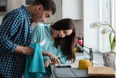 Pares jovenes que parecen sorprendidos el smartphone en el interior de la cocina Foto de archivo