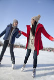 Pares jovenes que patinan en la pista de hielo, llevando a cabo las manos Imagen de archivo libre de regalías