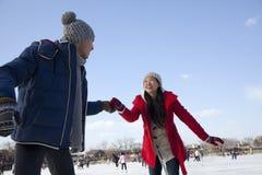 Pares jovenes que patinan en la pista de hielo, llevando a cabo las manos Imagen de archivo