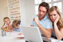 Pares jovenes que piensan y que miran un ordenador fotografía de archivo libre de regalías