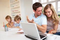 Pares jovenes que piensan y que miran una computadora portátil foto de archivo