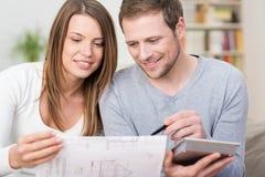 Pares jovenes que planean una nueva compra Foto de archivo libre de regalías