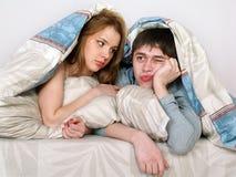 Pares jovenes que ponen en cama junto foto de archivo libre de regalías