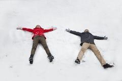 Pares jovenes que ponen en la nieve que hace ángeles de la nieve Fotografía de archivo libre de regalías