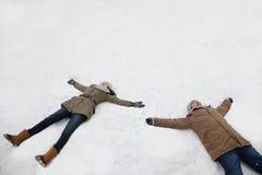 Pares jovenes que ponen en la nieve que hace ángeles de la nieve Foto de archivo libre de regalías