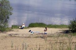 Pares jovenes que ponen en la playa arenosa en la orilla de mar en día soleado imagen de archivo libre de regalías