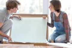 Pares jovenes que ponen juntos los muebles de la asamblea del uno mismo imágenes de archivo libres de regalías