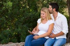 Pares jovenes que practican surf el web al aire libre con la tableta digital Imagen de archivo libre de regalías