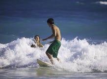 Pares jovenes que practican surf en Hawaii Imagenes de archivo