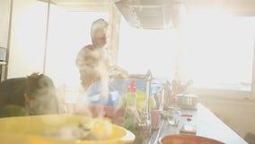 Pares jovenes que preparan el almuerzo en la cocina metrajes