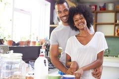 Pares jovenes que preparan el desayuno en cocina junto Imagen de archivo libre de regalías