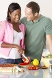 Pares jovenes que preparan la comida en cocina Imagenes de archivo
