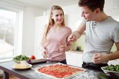 Pares jovenes que preparan la pizza en la cocina Imagen de archivo libre de regalías