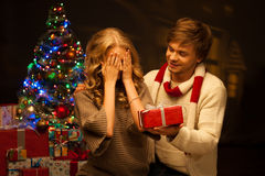 Pares jovenes que presentan el regalo de la Navidad Fotos de archivo libres de regalías