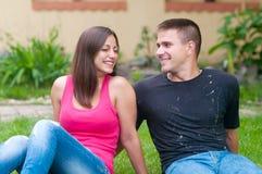 Pares jovenes que ríen divirtiéndose mientras que se sienta en jardín Imagen de archivo libre de regalías