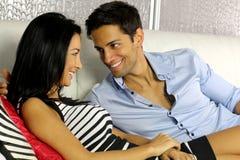 Pares jovenes que ríen en un sofá blanco Foto de archivo libre de regalías