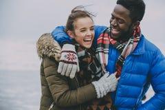 Pares jovenes que ríen en una playa del invierno Imagen de archivo
