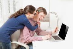 Pares jovenes que ríen ruidosamente detrás del ordenador portátil de la oficina Fotos de archivo libres de regalías