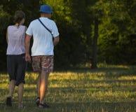 Pares jovenes que recorren abajo del prado Imagen de archivo libre de regalías