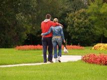 Pares jovenes que recorren en el parque Imagen de archivo