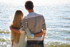 Pares jovenes que recorren en la playa Imagen de archivo
