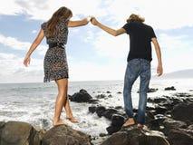 Pares jovenes que recorren en la playa Foto de archivo libre de regalías