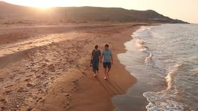 Pares jovenes que recorren en la playa almacen de video