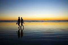 Pares jovenes que recorren en la playa romántica en la puesta del sol Fotos de archivo libres de regalías