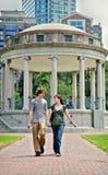 Pares jovenes que recorren en parque de la ciudad foto de archivo libre de regalías