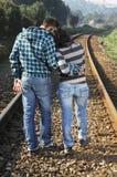 Pares jovenes que recorren en una pista ferroviaria imagenes de archivo