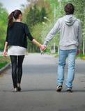 Pares jovenes que recorren junto en parque Foto de archivo libre de regalías
