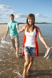 Pares jovenes que recorren a lo largo de línea de la playa Imagen de archivo