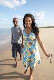 Pares jovenes que recorren a lo largo de línea de la playa Imagenes de archivo