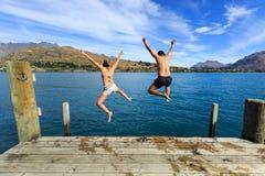 Pares jovenes que saltan al borde de un muelle adentro al lago Foto de archivo libre de regalías