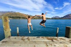 Pares jovenes que saltan al borde de un muelle adentro al lago Imagen de archivo libre de regalías